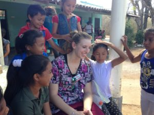 U-M Dearborn student Natasha Hampton relaxes with children in Honduras after giving fluoride treatments and helping them learn to brush. The Lincoln Park senior joined other UM-Dearborn students as part of a medical brigade building public health facilities. Photo by Marilee Benore