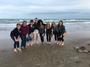 """After writing """"SPH"""" and a block """"M"""" in the sand, School of Public Health spring break students take a photo at South Padre Island upon their arrival for a community health assessment project in Hidalgo County, Texas. They are, from left, Liz Timoszyk, Elana Elkin, Peggy Korpela, Christopher Bush, Megan Edmonds, Chelsea Abshire, Grace Christensen and Julia Porth. Photo Courtesy of the School of Public Health"""