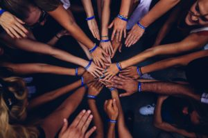 """A circle of many people wearing """"Emfasis"""" bracelets outstretch their hands to meet in the center of the circle."""