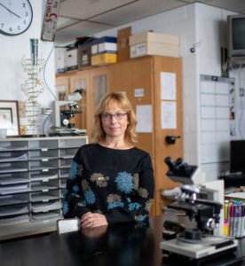 Racquel Huddleston stands in her lab, looking slightly to the right of the camera with a slight smile.
