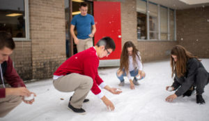 A few students squat in the snow, collecting enough to put in petri dishes.