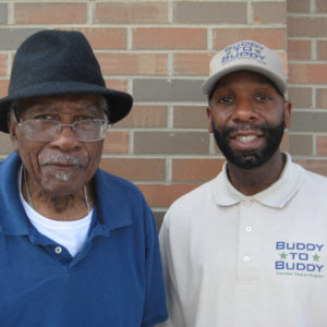 Buddy to Buddy employee stands next to WWII veteran, both smiling.