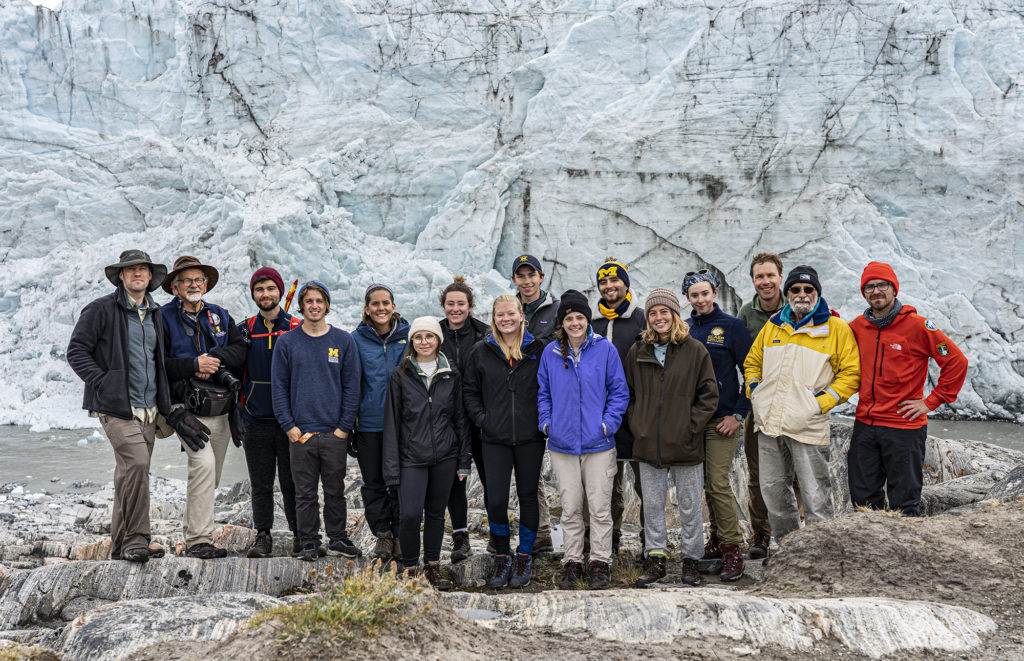 A group of people pose in front of a glacier.