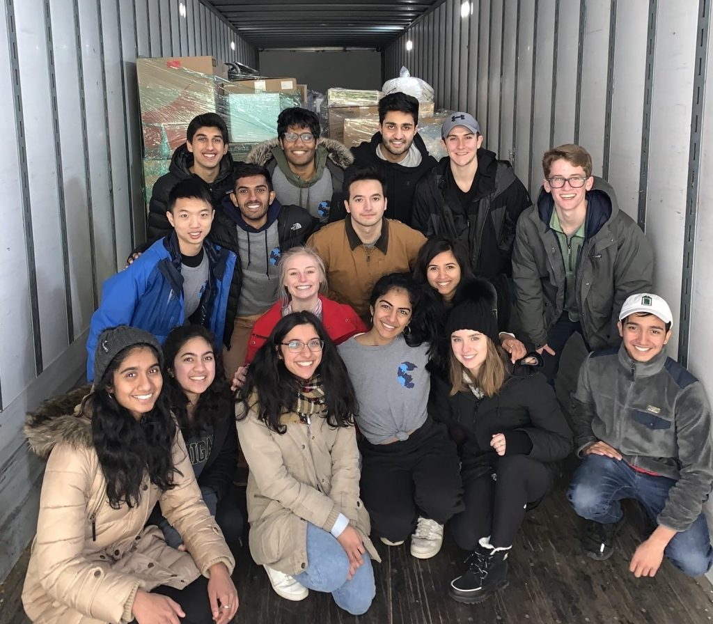 A group of students pose together inside a box truck with supplies in the background.