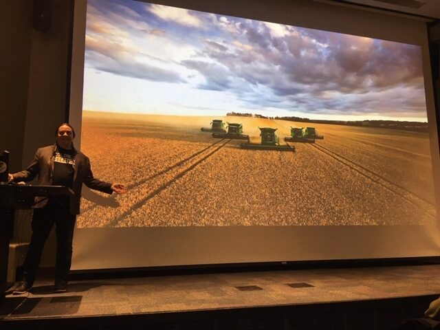 Sherman gestures to a screen showing a picture of machines plowing a field.