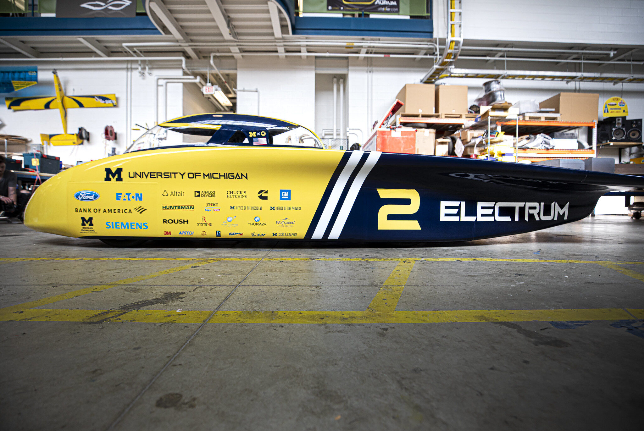 Large solar car parked in garage.