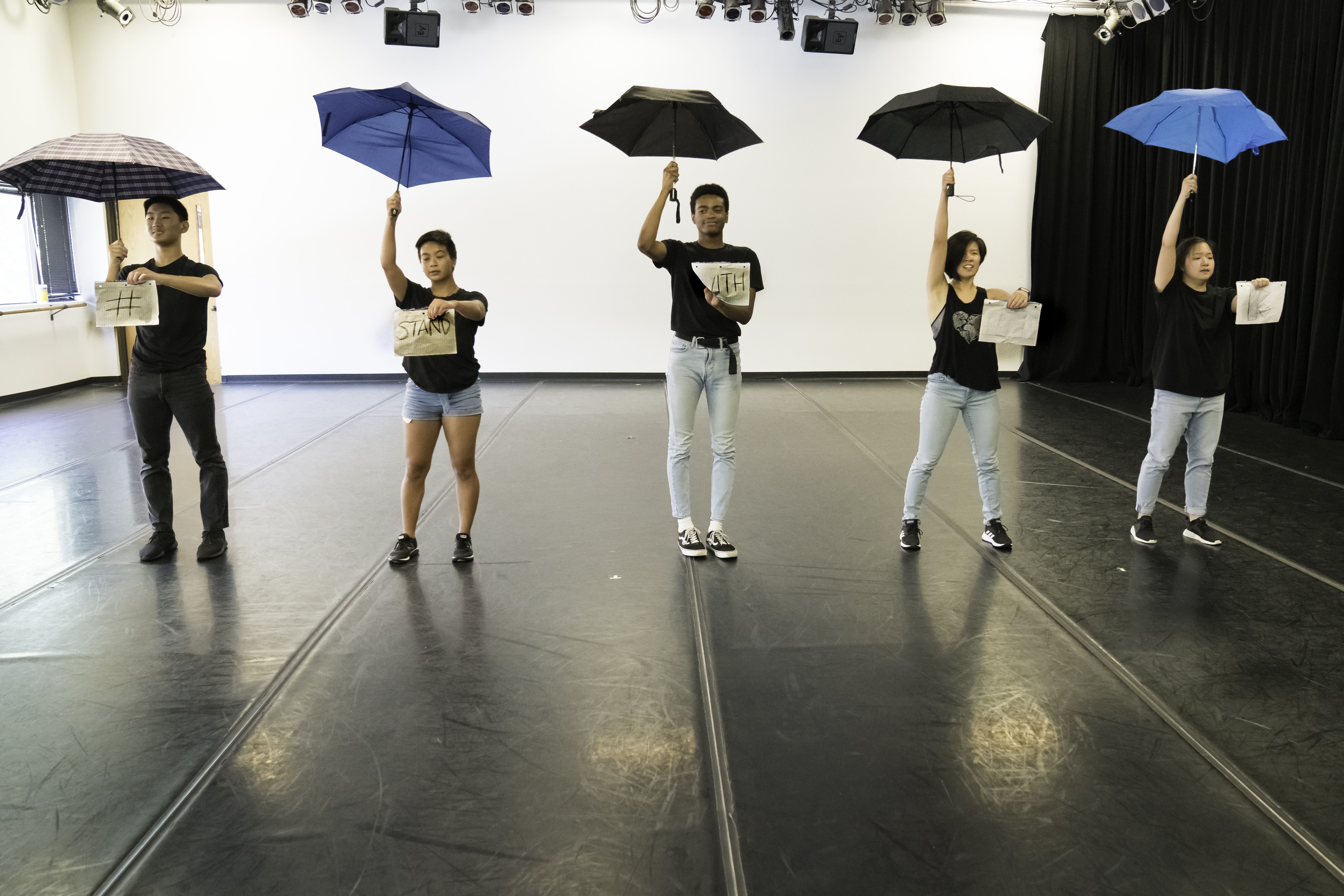 Four students stand with signs in front of them on one hand and umbrellas open and up in the other hand on a practice stage.