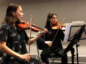 Two female students perform with their violins.