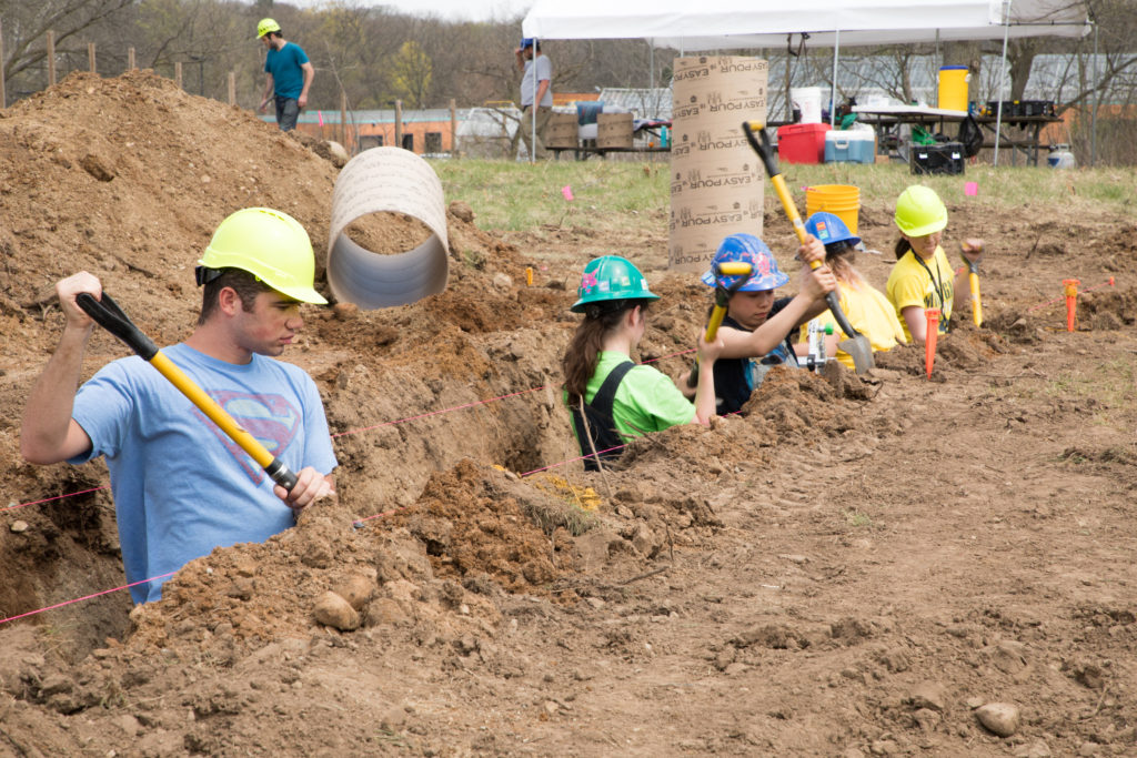 Five students in multicolored construction helmets stand in man-made ditch digging the foundation for the building