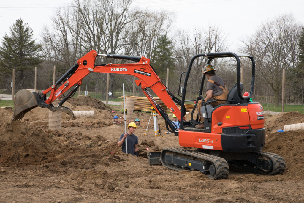 Man sitting in excavator converses with another man digging in a hole that has been dug nearby