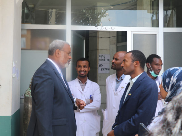 University of Michigan Provost Martin Philbert converses with doctors outside of a hospital in Africa.