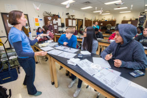 LSA Outreach Coordinator Jenna Munson guides students through an interactive science activity. From left are Keegan Beznoska, Jeiny Tavarez and Cung Bawi. (Photo by Peter Matthews, Michigan Photography)