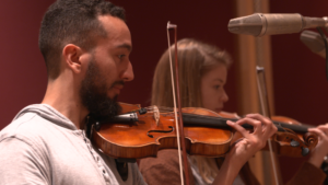 A male and female student play their violins with great focus.