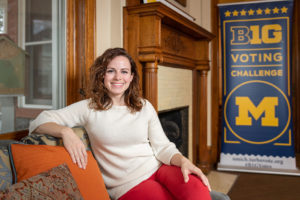 Erin Byrnes sits on a couch in the Ginsberg Center, smiling at the camera with a Big 10 Voting Challenge sign in the background.