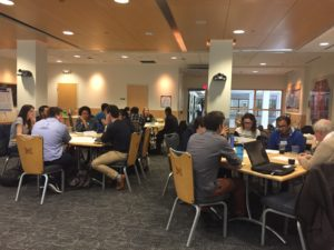 Students, faculty and staff are seated at various tables around a large room.