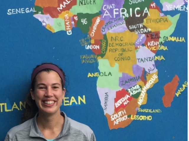 Boyle stands in front of a wall painted with the continent Africa.