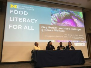 "Panel sits in front of screen that reads ""Food Literacy for All."""