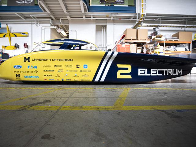 Large solar car parked in garage.