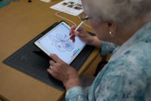 Rosalind paints fruit on an iPad.