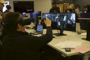 """Student has on headset to virtually operate a camera and uses hand monitors to """"operate"""" the camera"""