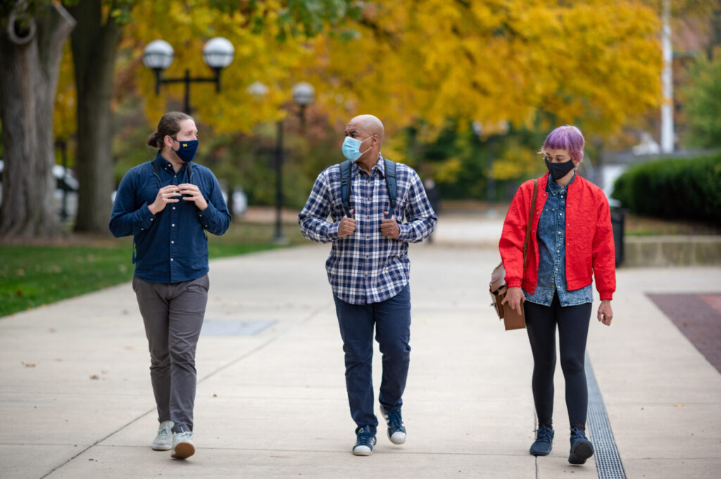 Three people walk side by side outside at the U-M campus wearing face masks and talking.