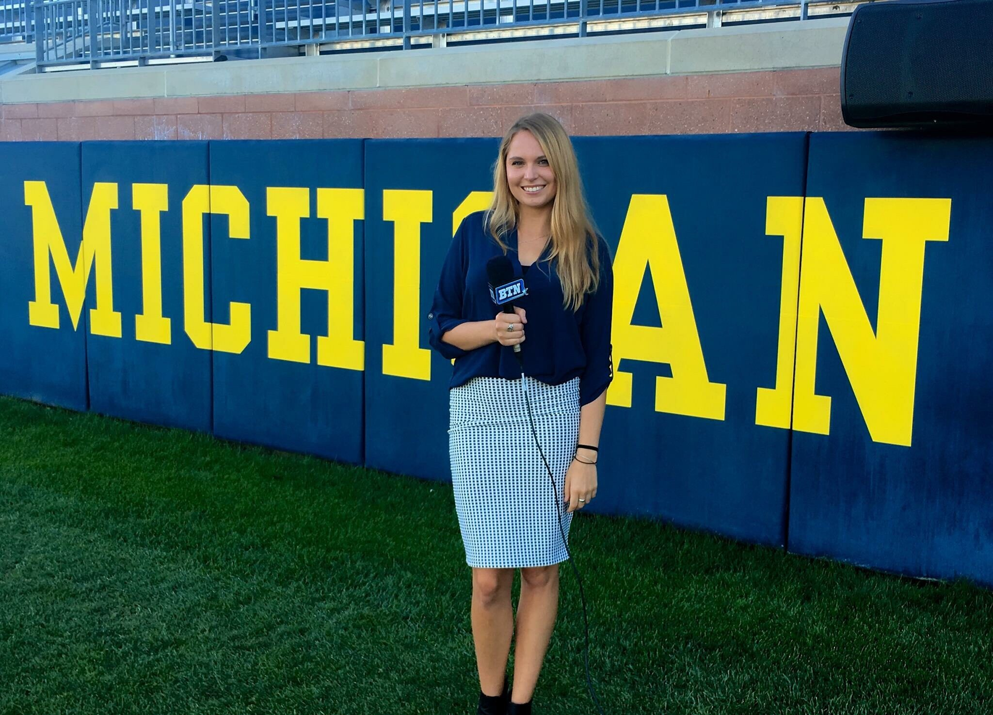 """Riley Nelson stands in front of word """"Michigan"""" in Michigan Football Stadium"""