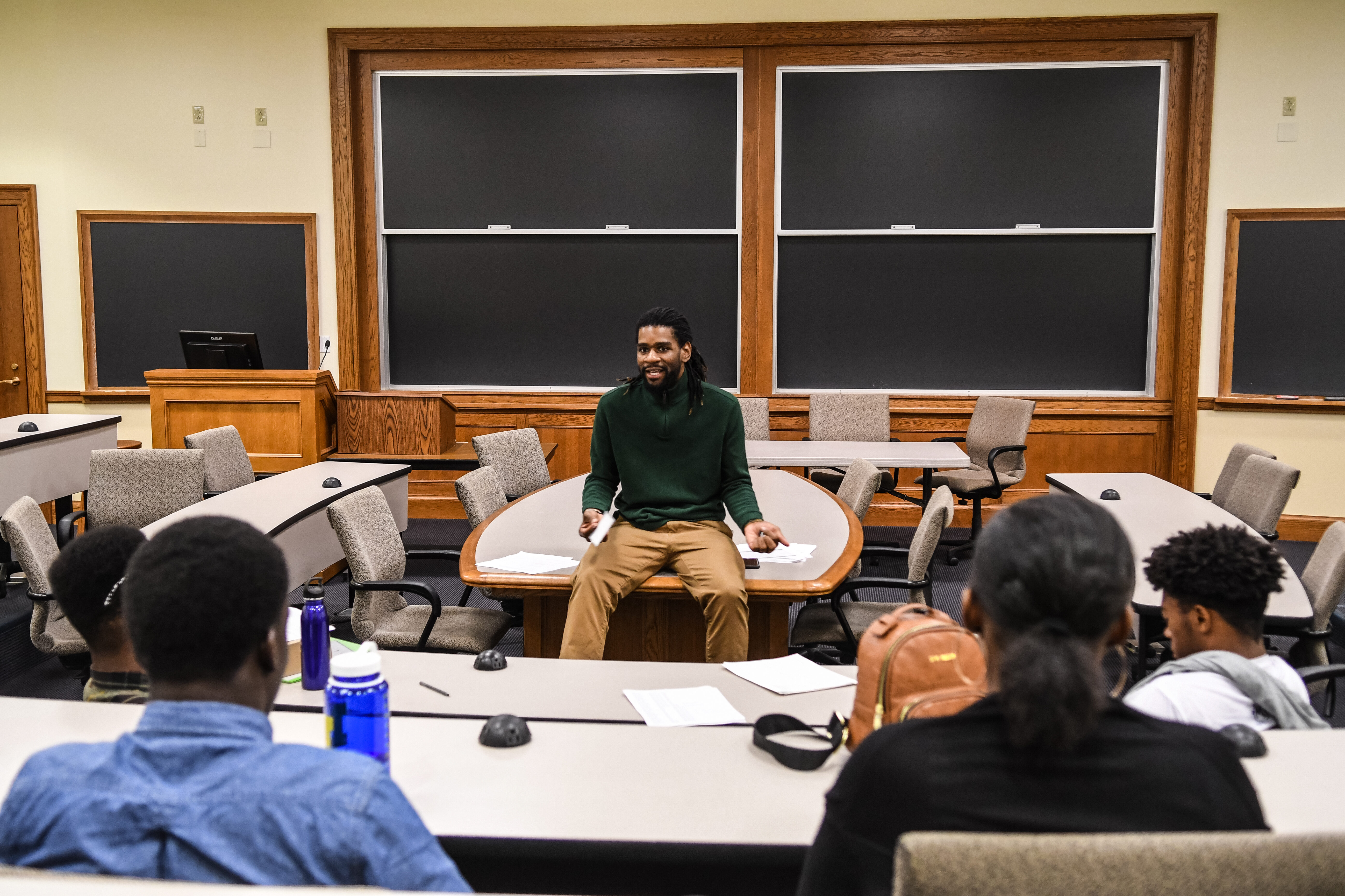 An instructor (shown from front) sits on a table, addressing students (shown from back) sitting at desks across from him.