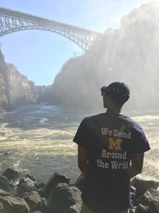 "A young man sits in front of a mountainous landscape wearing a shirt that reads ""We send M around the world."""